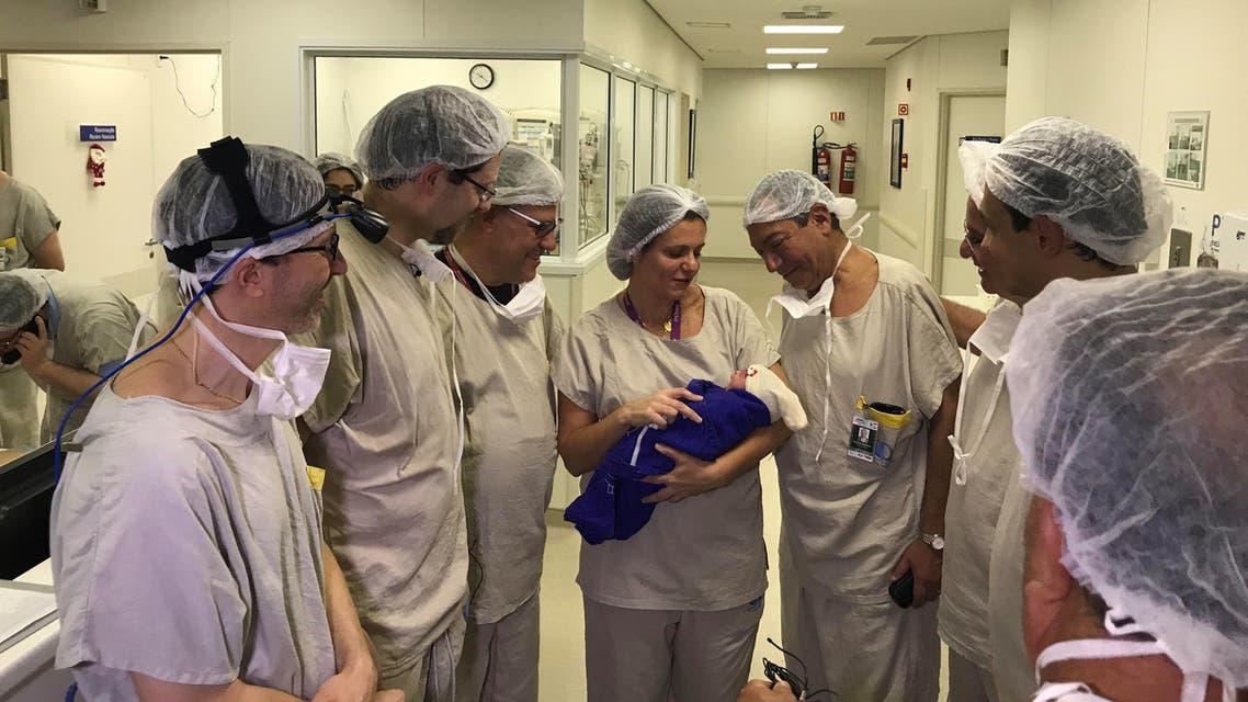 فريق طبي يحمل الطفل الأول الذي ولد عن طريق عملية نقل الرحم من متبرعة متوفية في مستشفى ساو باولو في 15 ديسمبر 2017 في هذه الصورة التي تم الحصول عليها في 4 ديسمبر 2018
