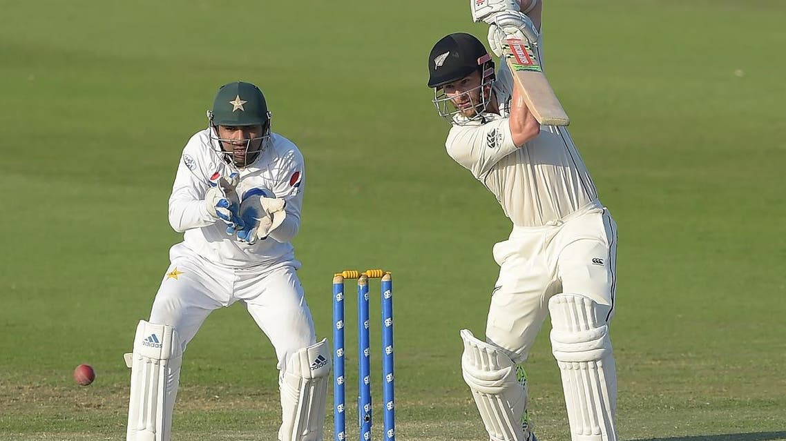 New Zealand captain Kane Williamson (R) plays a shot as Pakistani wicketkeeper captain Sarfraz Ahmed (L) looks on during the fourth day of the third and final Test cricket match between Pakistan and New Zealand in Abu Dhabi. (AFP)