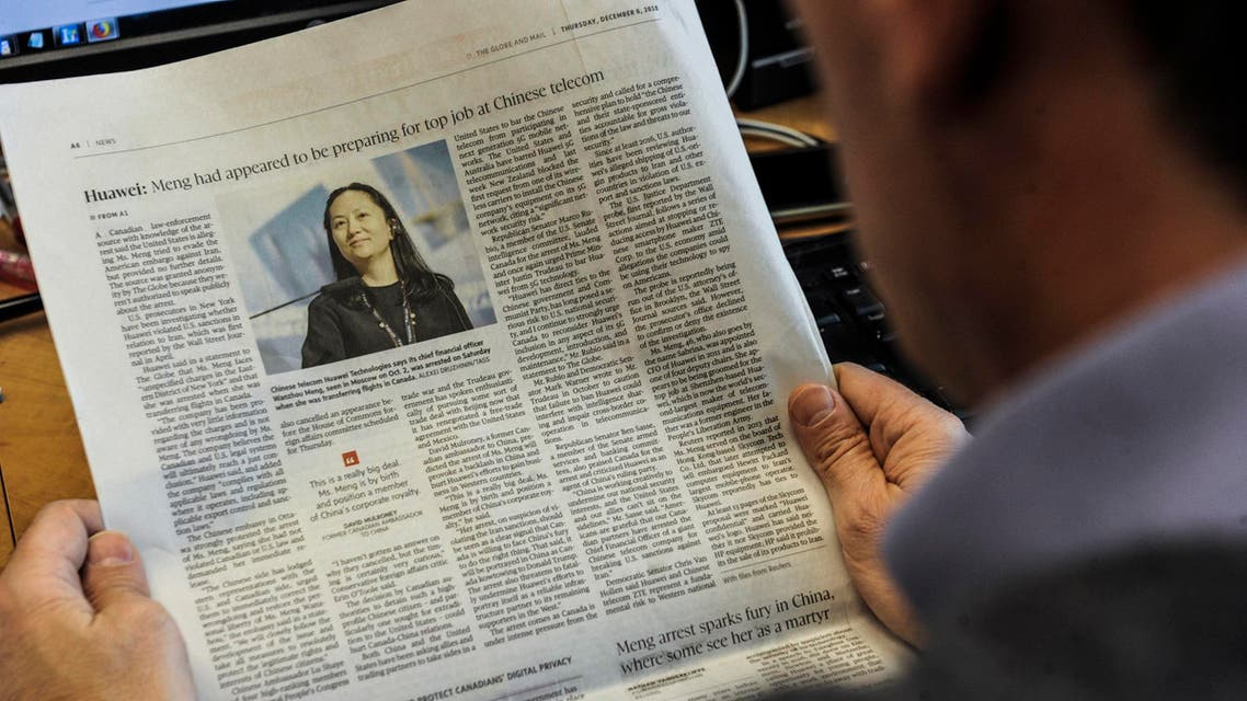 An illustration shows a journalist reading a news page about tech giant Huawei in The Globe and Mail in Montreal, Canada, on December 6, 2018. (AFP)
