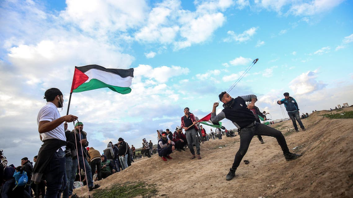 A Palestinian protester uses a slingshot to hurl objects during clashes following a demonstration along the border with Israel east of Gaza City, during clashes following a border demonstration on December 7, 2018.