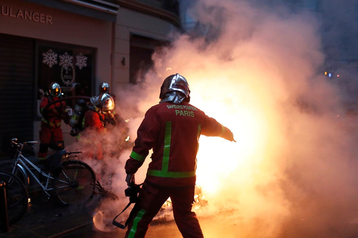 Firefighters try to extinguished a car set on fire by demonstrators during clashes with riot police in Paris. (AP)