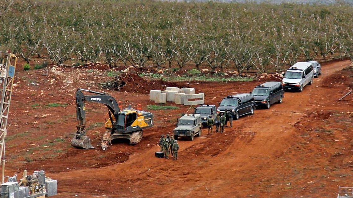 A picture taken on December 5, 2018 from a position near the southern Lebanese village of Kfar Kila shows members of the Israeli military, excavators, trailers, and other vehicles operating on the other side of the border. (AFP)