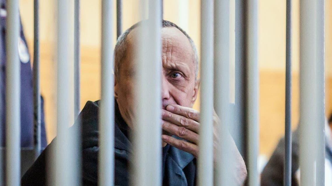 Mikhail Popkov sits inside a defendants' cage during a court hearing in Irkutsk on December 10, 2018. (AFP)
