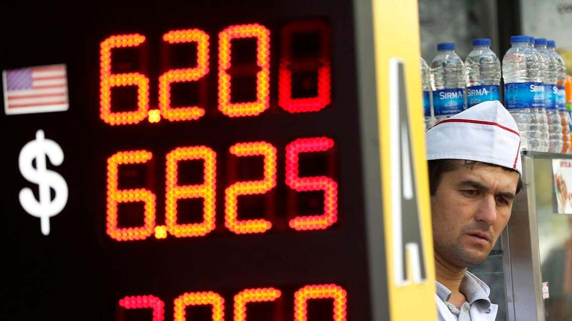 A restaurant worker peers from his shop next to a board with foreign currency exchange rates outside a currency exchange shop in Istanbul. (File photo: AP)
