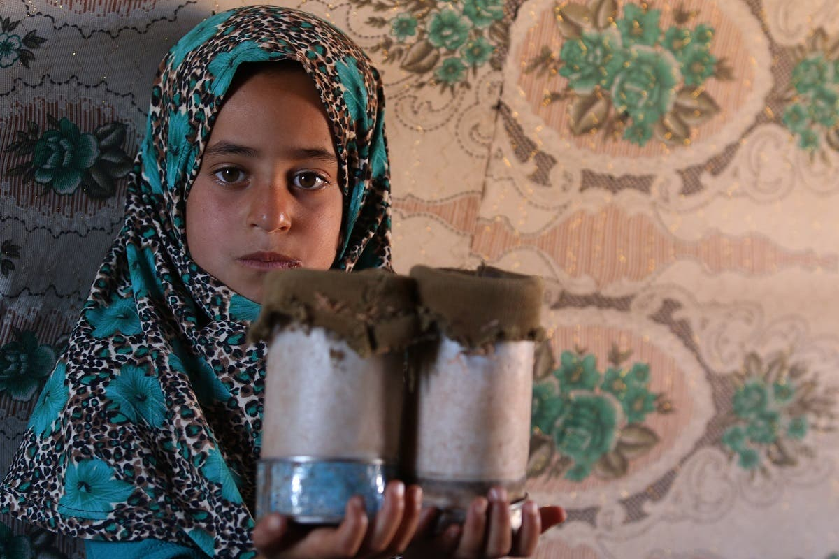 Eight year-old Maya Mohammad Ali Merhi, shows her prosthetic legs made by her father from tin cans. (AFP)