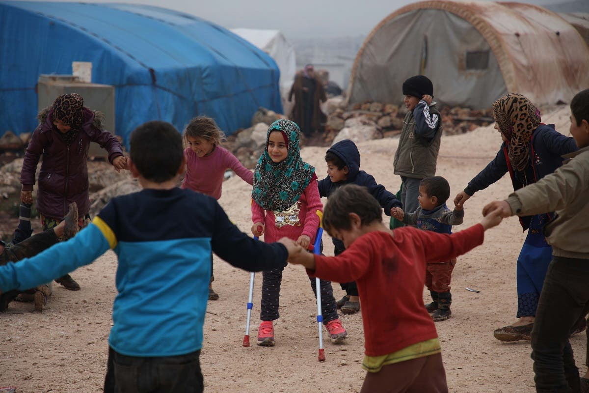 Syrian Maya Merhi (L) stands with her friends in the Internally Displaced Persons (IDP) camp of Serjilla in northwestern Syria. (AFP)