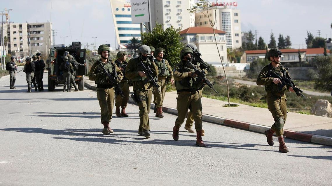 Israeli soldiers conduct a search for suspects of a shooting attack yesterday in the West Bank City of Ramallah. (AP)