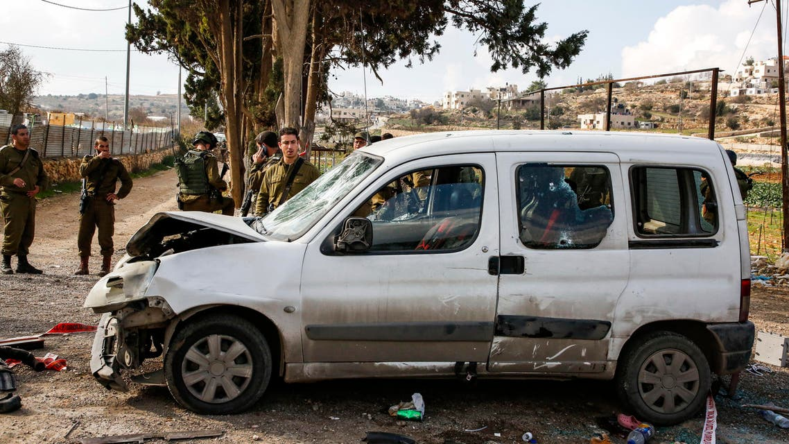 Israeli soldiers standing by a damaged car at the scene of an attack where a Palestinian man rammed a vehicle into three Israeli soldiers  on November 26, 2018. (AFP)