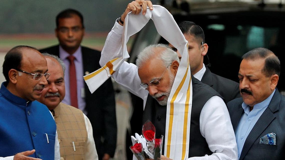 India's PM Modi Modi removes a stole given to him by a minister upon his arrival at the Parliament on the first day of the winter session in New Delhi. (Reuters)