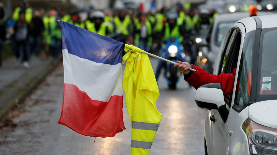 """A protester holds a French flag and a yellow vest from a car during a demonstration by the """"yellow vests"""" movement in Somain, France, December 8, 2018. REUTERS/Pascal Rossignol"""
