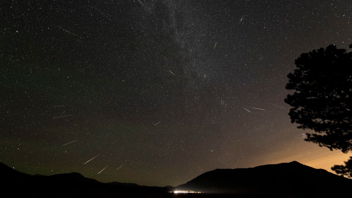 A Perseid meteor is seen over Rocky Mountain National Park in Colorado in the early morning hours of August 13, 2018, competing with lights from vehicles on nearby roads. The annual Perseid meteor shower peaks in the early August. The green sky is airglow, a phenomenon of the upper atmosphere seen at night.