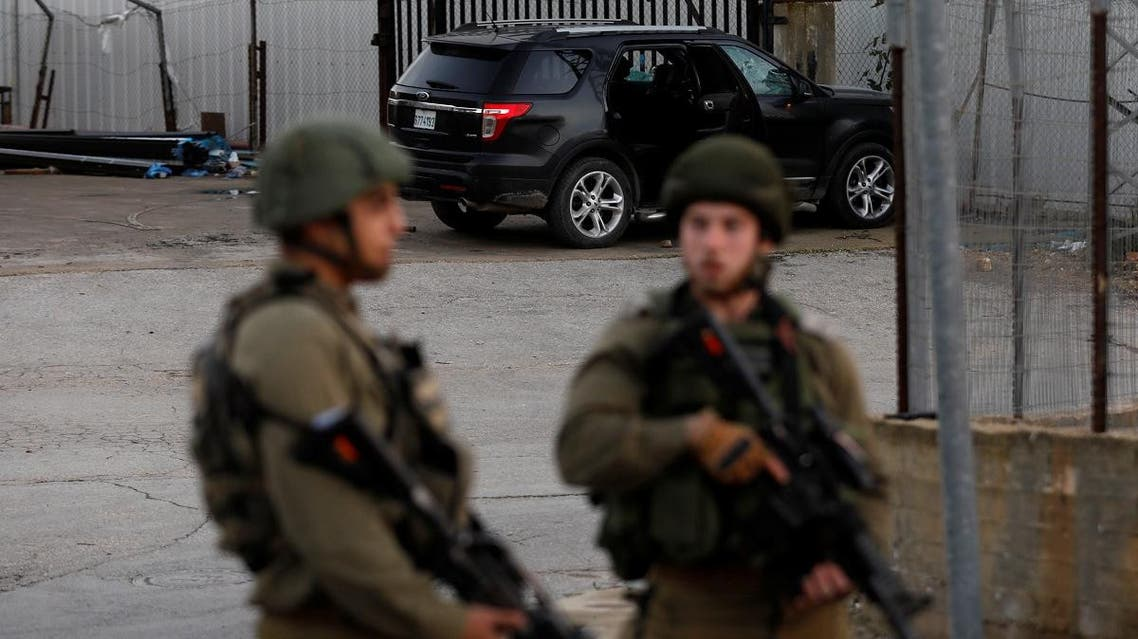 A vehicle is seen at the scene of an incident as Israeli soldiers stand guard near Ramallah, in the Israeli-occupied West Bank on December 13, 2018. (Reuters)