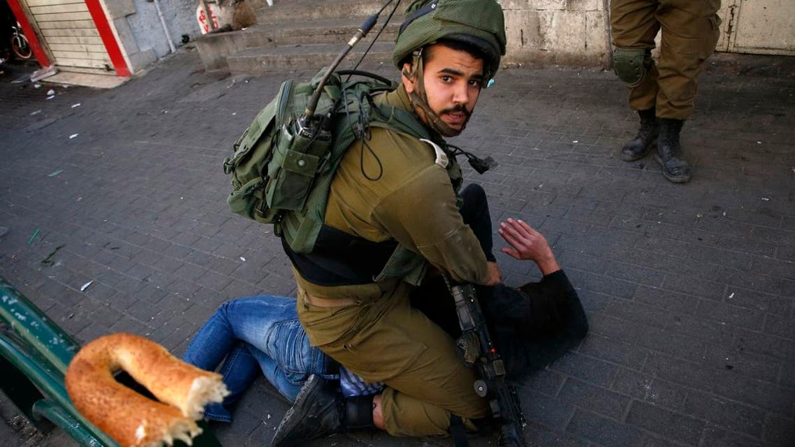 Israeli soldiers arresting Palestinian in West Bank (AFP)