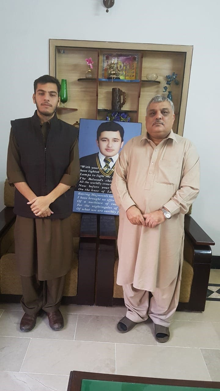 Mr Muhammad Tufail Khattak along with his son, Ahmad Shah. In the middle a portrait of his martyred son, Sher Shah. (Supplied)
