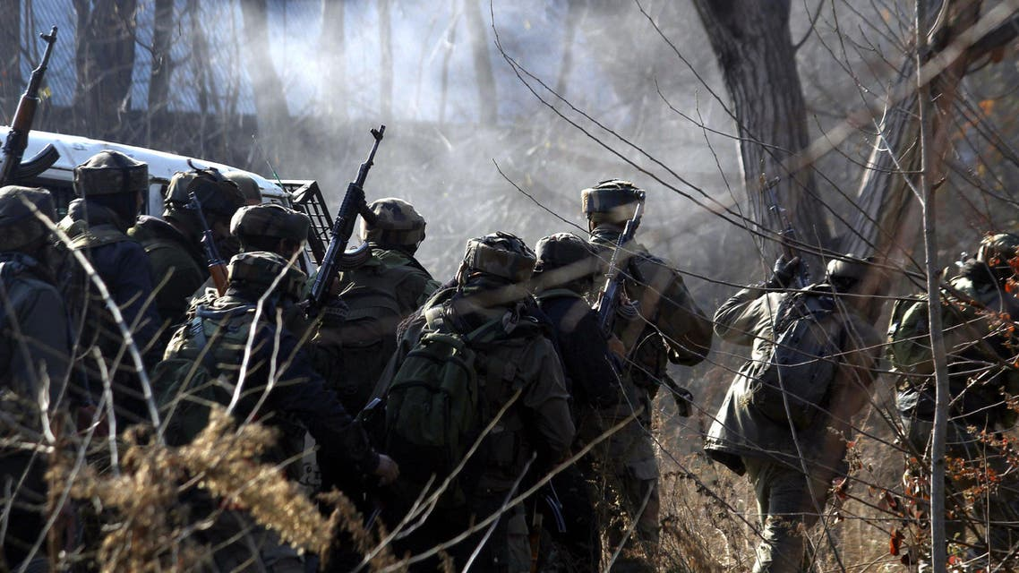 Indian army soldiers take cover near the site of a gun-battle between militants and government forces in Sirnoo Pulwama south of Srinagar on December 15, 2018. (AFP)