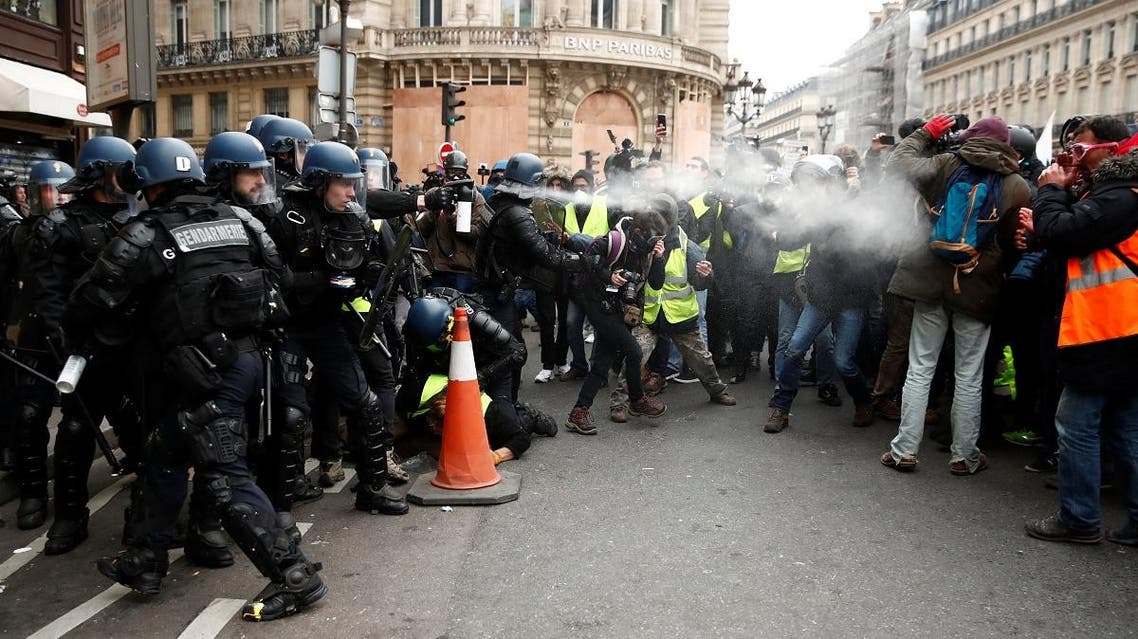 """French gendarmes use pepper spray to push back protesters wearing yellow vests during a demonstration near the Opera House as part of the """"yellow vests"""" movement in Paris. (Reuters)"""