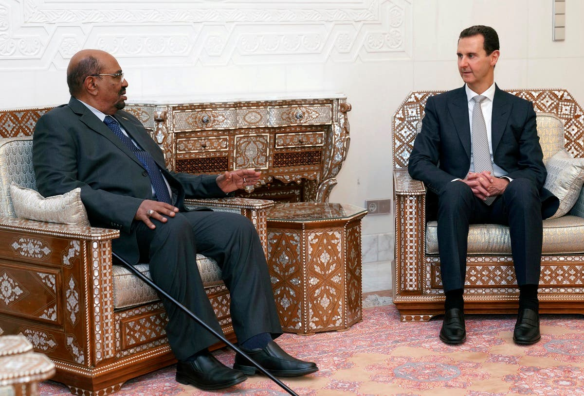 In this photo released by the Syrian official news agency SANA, Syrian President Bashar Assad, right, meets with Sudan's President Omar al-Bashir in Damascus, Syria, Sunday, Dec. 16, 2018. (SANA via AP)