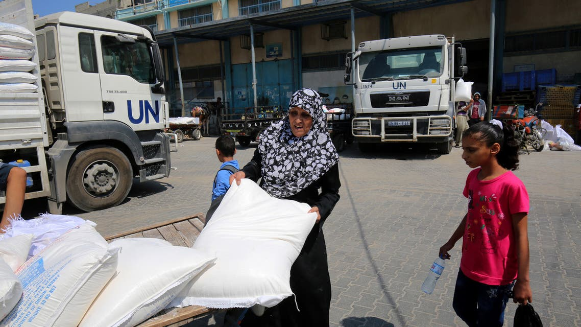 "A Palestinian woman takes a bag of flour outside an aid distribution center run by the United Nations Relief and Works Agency (UNRWA), in Khan Younis in the southern Gaza Strip ,on September 4, 2018. The UN agency for Palestinian refugees (UNRWA) has been a lifeline for millions of Palestinians since it was set up nearly 70 years ago. On August 31, the United States, by far the biggest contributor to the agency, announced it was halting its funding to the organisation, which it labelled ""irredeemably flawed""."