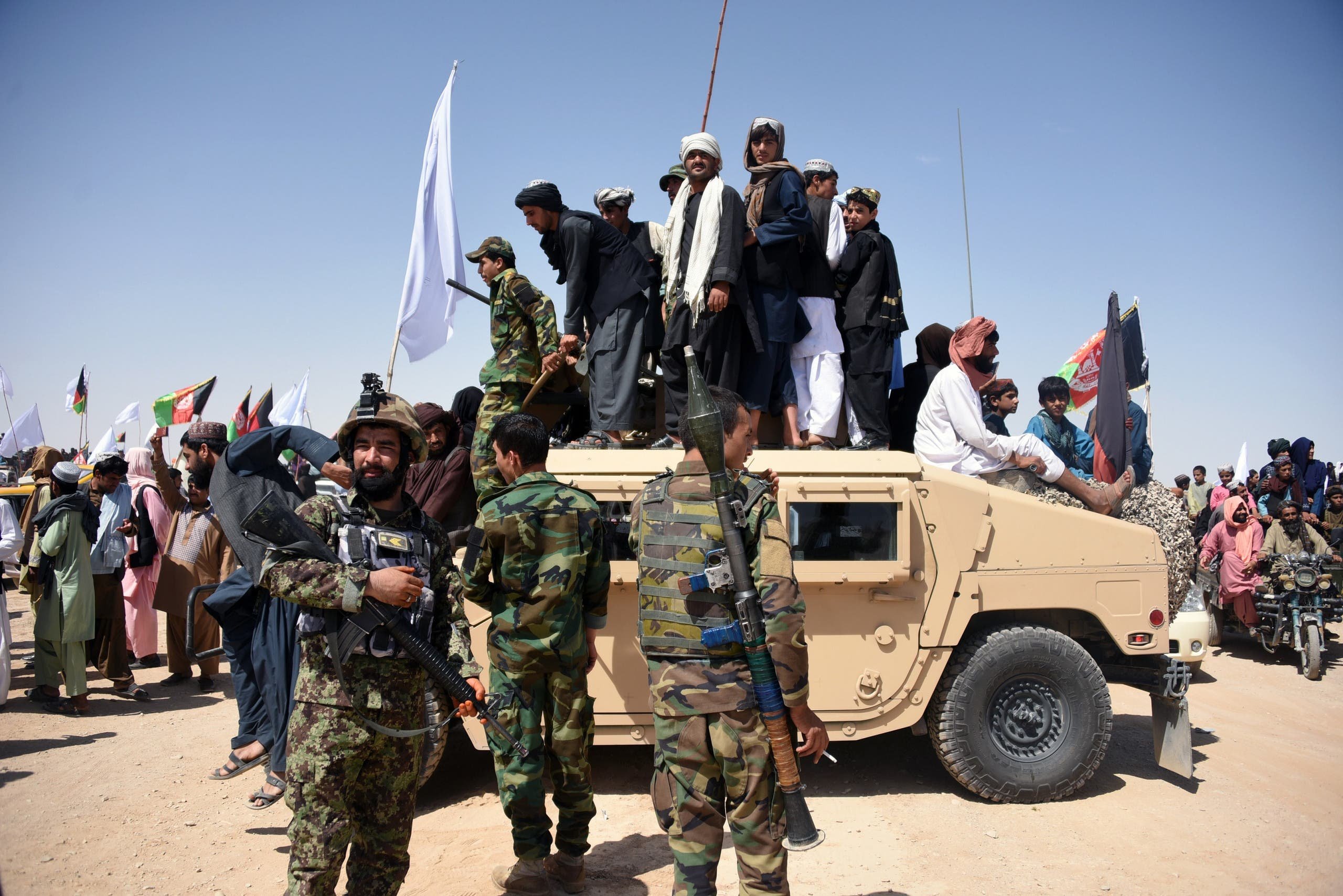 Afghan Taliban militants and residents stand on an armoured Humvee vehicle of the Afghan National Army (ANA) in Maiwand district of Kandahar province on June 17, 2018. (AFP)