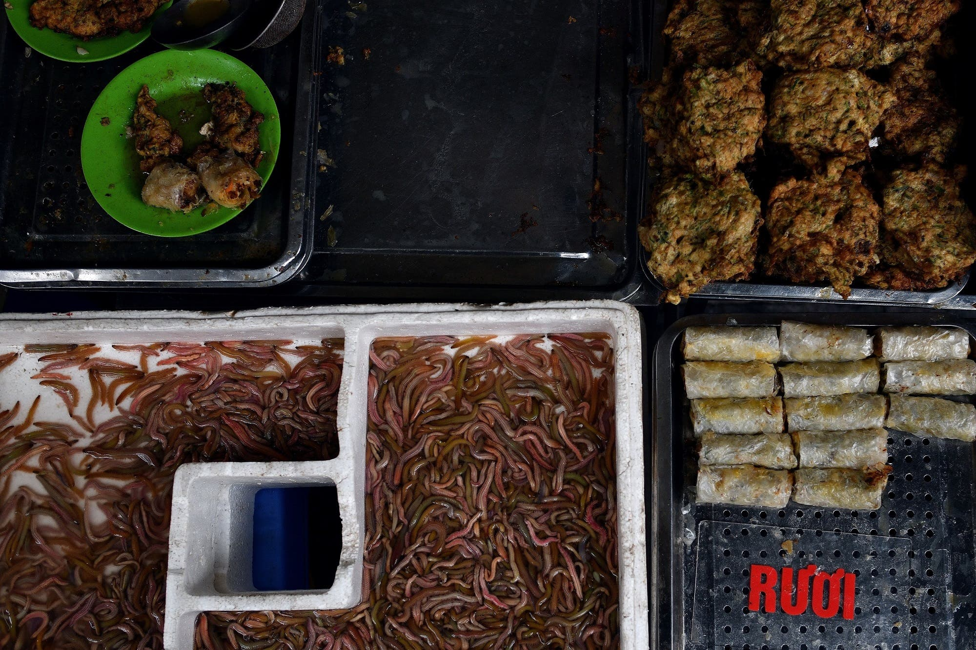 'Cha ruoi' ragworms and fritters on a tray at a street food stall in the old quarters of Hanoi on December 14, 2018. (AFP)