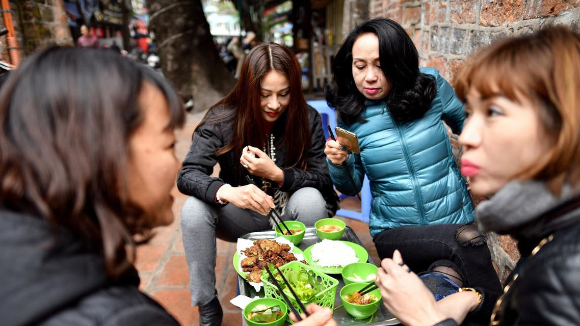 Vietnamese women eating 'cha ruoi' ragworms fritters at a street food stall in the old quarters of Hanoi on December 14, 2018. (AFP)