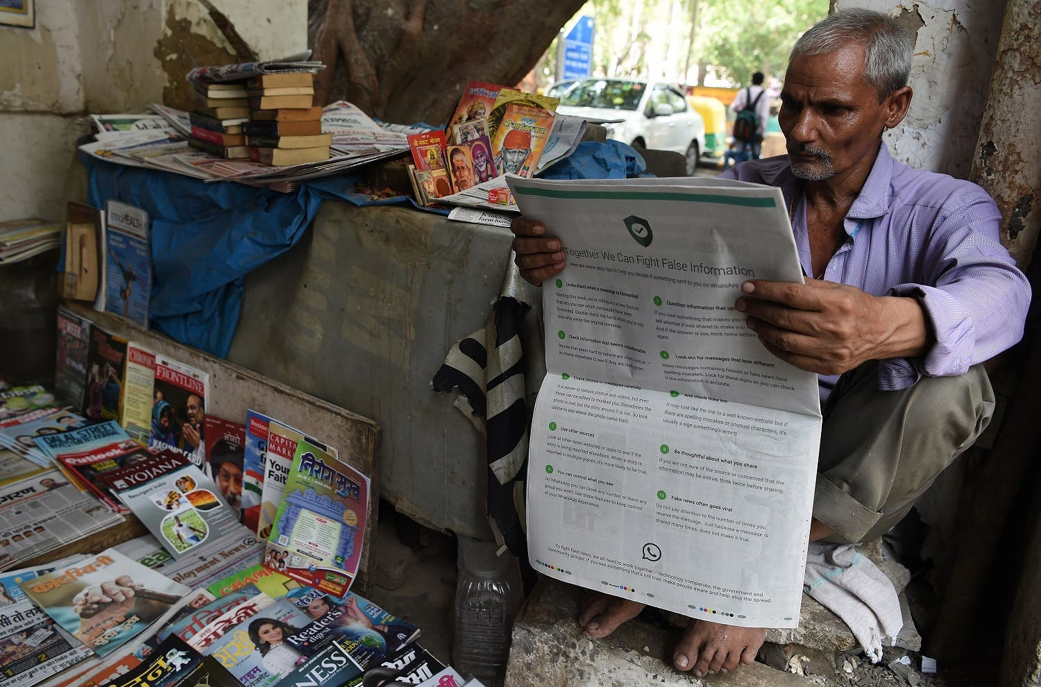 A vendor reading a newspaper with a full back page advertisement from WhatsApp intended to counter fake information in New Delhi on July 10, 2018. (AFP)