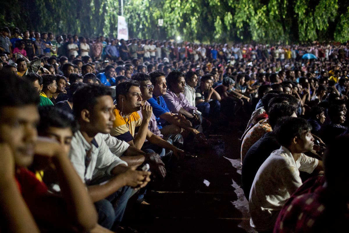 Bangladeshi people watch the live broadcast of the World Cup final match between France and Croatia on a screen in Dhaka, Bangladesh. (AP)