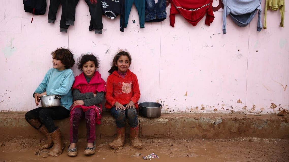 Syrian girls sit with their mudied boots beneath a laundry line next to a temporary shelter, at a camp for the displaced near the village of Shamarin, near the border with Turkey in the northern Aleppo province. (AFP)