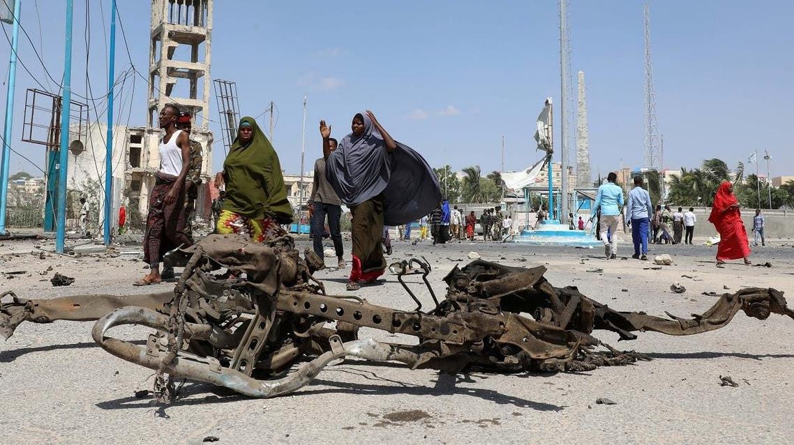 Somali women walk past car wreckage after explosion near president's residence in Mogadishu. (Reuters)
