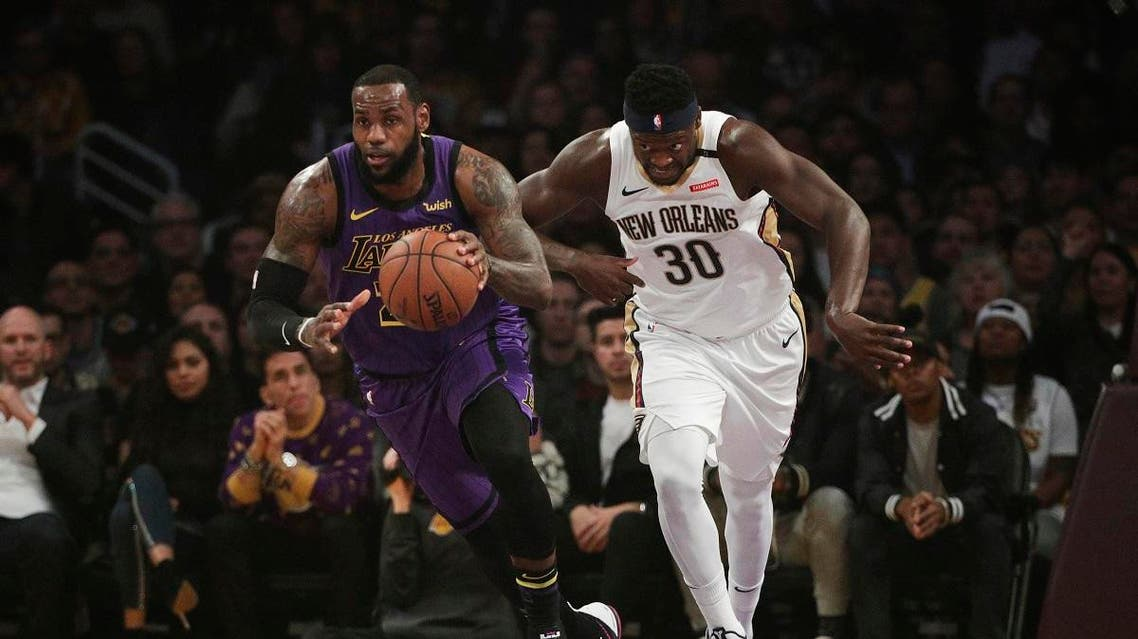 Los Angeles Lakers' LeBron James, left, dribbles the ball past New Orleans Pelicans' Julius Randle during the first half of an NBA basketball game. (AP)