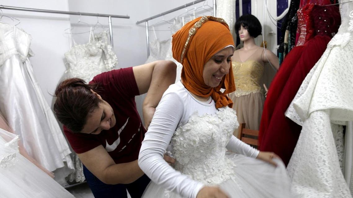Nadia Mohammad Salem tries on a wedding dress in Cairo. (Reuters)
