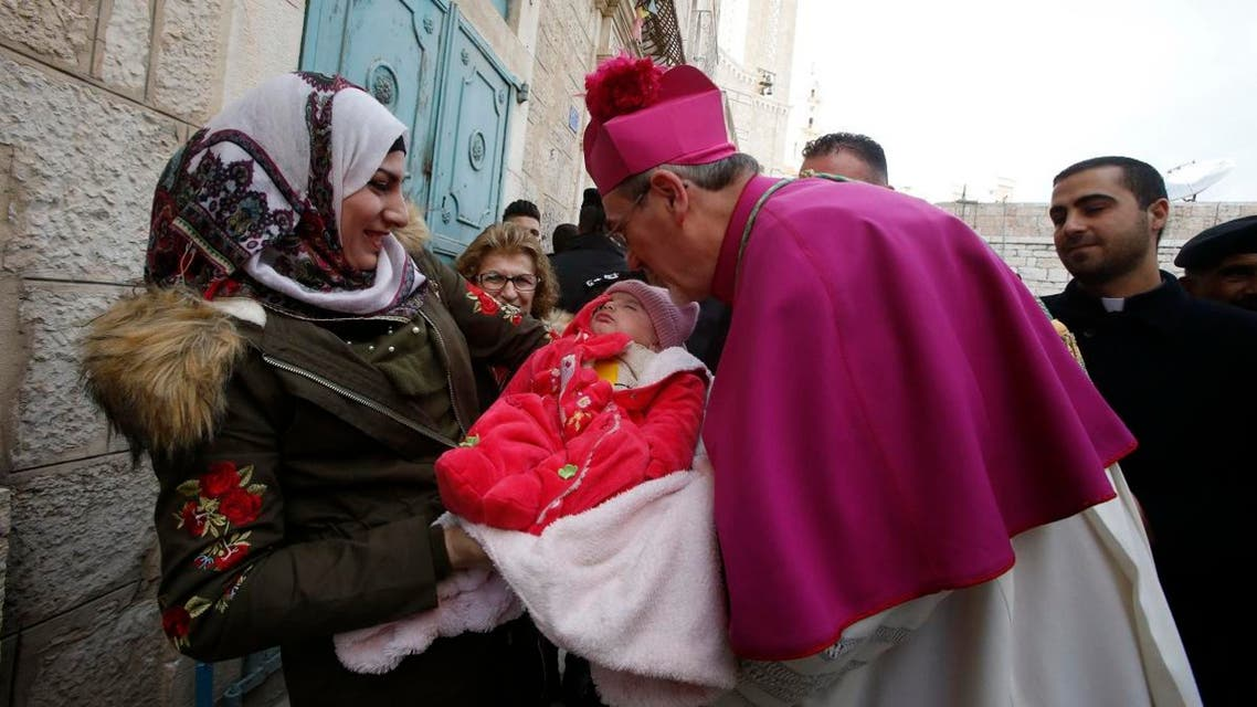 Latin Patriarch of Jerusalem Pierbattista Pizzaballa greets a Muslim Palestinian woman and a baby in the West Bank city of Bethlehem, on December 24, 2018. (AFP)