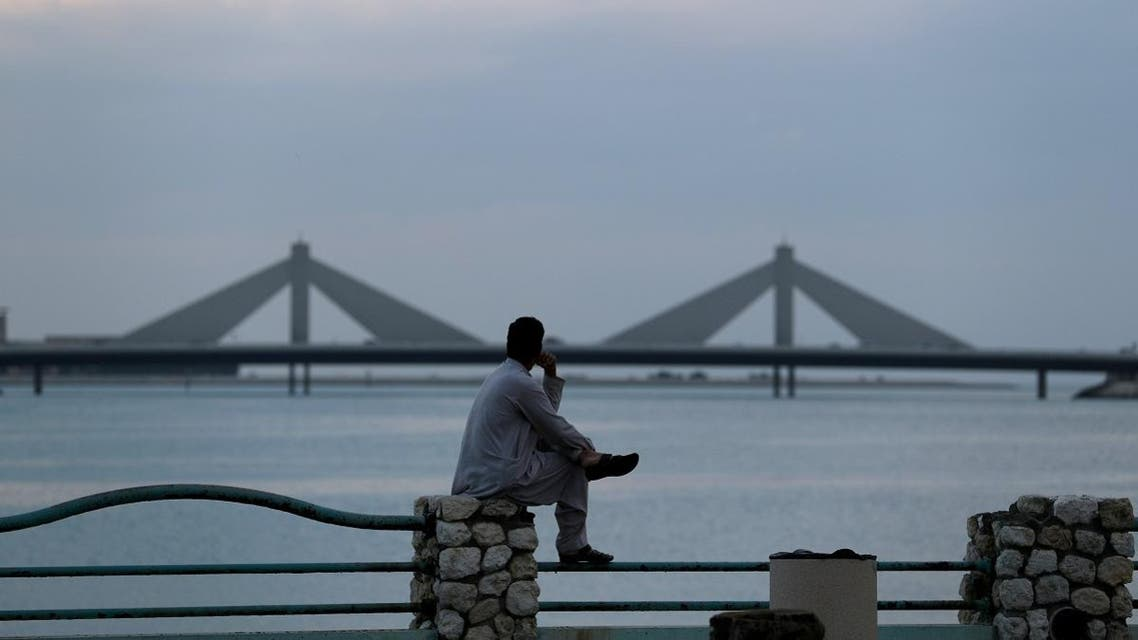 Man sits and looks towards the Sheikh Isa Causeway in Manama. (Reuters)