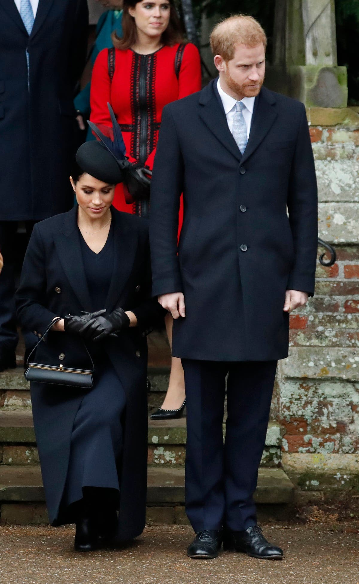 Britain's Prince Harry, stands with Meghan, Duchess of Sussex as she does a curtsy to Britain's Queen Elizabeth II as she leaves in a car after attending the Christmas day service. (AP)
