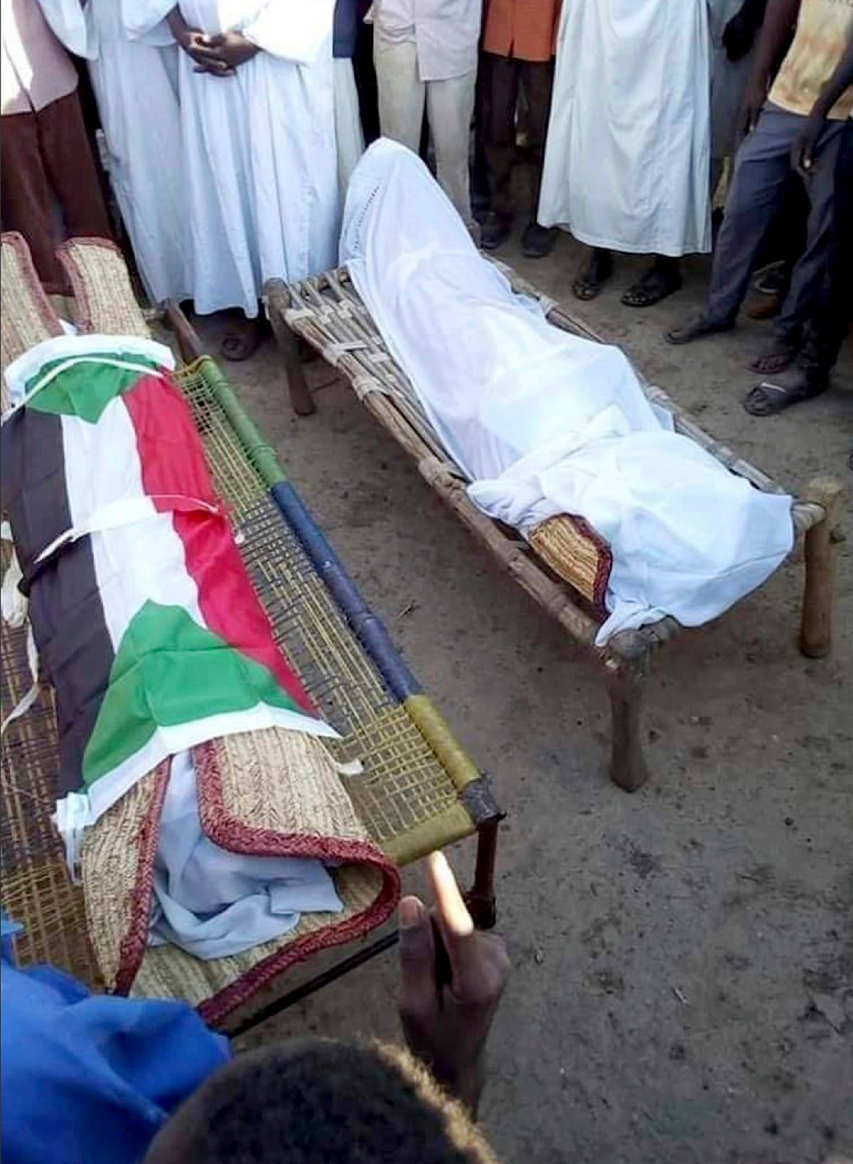 In this Friday Dec. 21, 2018 handout photo provided by a Sudanese activist, people pray in front of the bodies of 14-year old Mohammed Ismail and 10-year old Shawky Sadeq who were both killed during an anti-government protest. (AP)