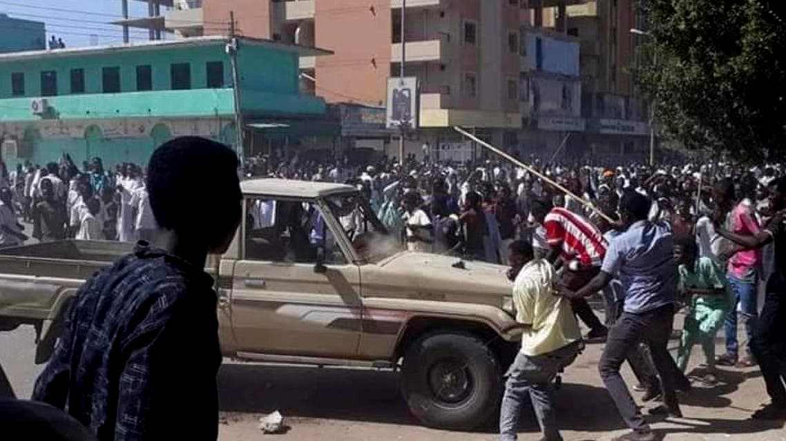 In this Sunday, Dec. 23, 2018 handout photo provided by a Sudanese activist, people chant slogans and attack a national security vehicle during a protest (AP)