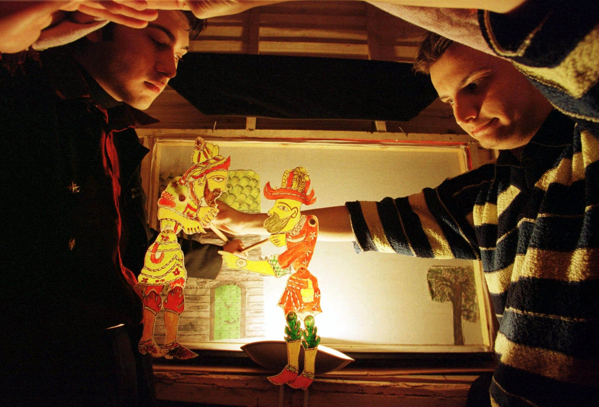Young Karagoz apprentices show the shadow puppets in Istanbul on January 5, 2000. (AP)