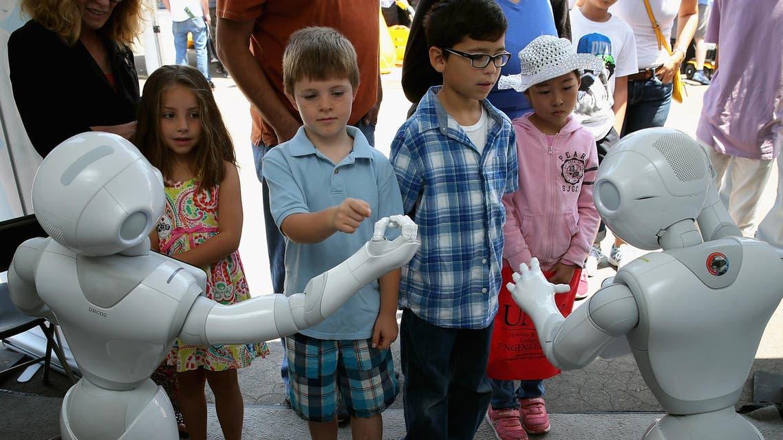 Children interact with Aldebaran's Pepper robot in California on June 6, 2015. (AFP)