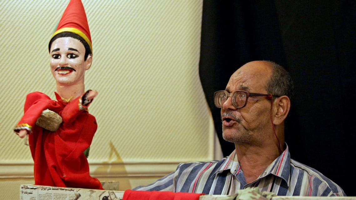 Egyptian puppeteer Mustafa Othman performs with his Aragoz puppet at the Egyptian National Theater in Cairo on 16 August 2004. (AFP)
