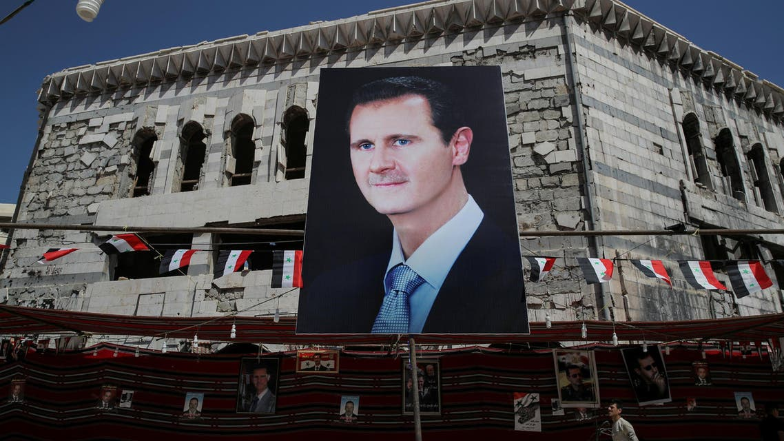 A man walks past a banner showing Syrian President Bashar al-Assad in Douma, outside Damascus on September 17, 2018. (Reuters)