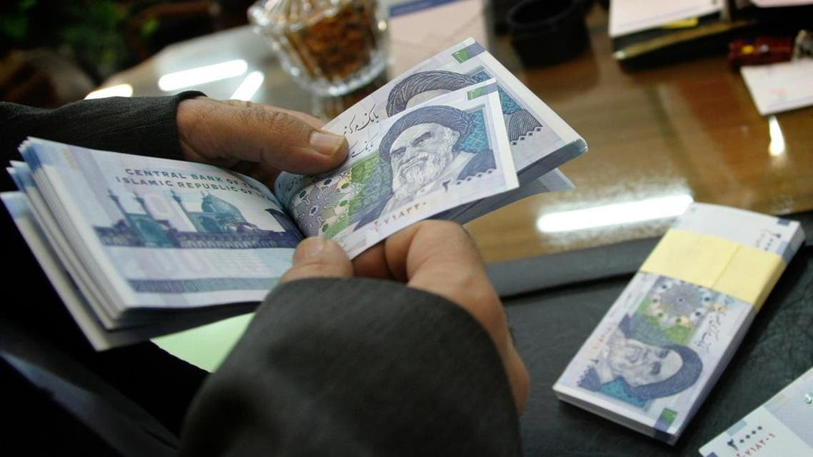 An Iranian bank teller counts new 20,000 rial notes at Iran's Central Bank in Tehran March 15, 2004. Iran began to release the new 20,000 rial note equivalent to $2.38 shortly before the Iranian new year which begins March 21. REUTERS/Morteza Nikoubazl CJF/AA