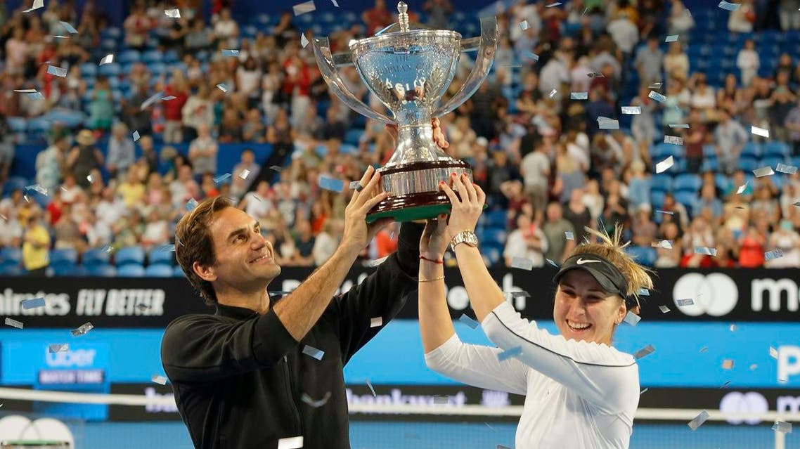 Switzerland's Federer and Bencic hold the trophy after winning the final against Germany at the Hopman Cup. (AP)