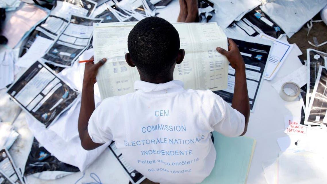 Man examines voting materials at CENI tallying centre in Kinshasa. (Reuters)