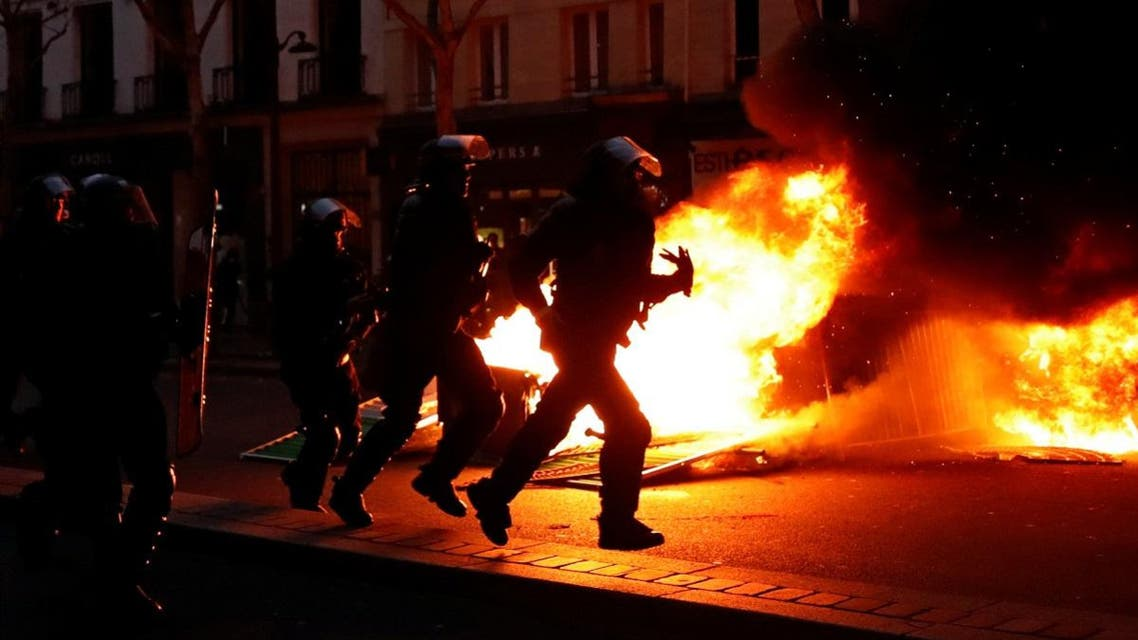 "Riot policemen run near a fire during a demonstration by the ""yellow vests"" movement at Boulevard Saint Germain in Paris, France. (Reuters)"