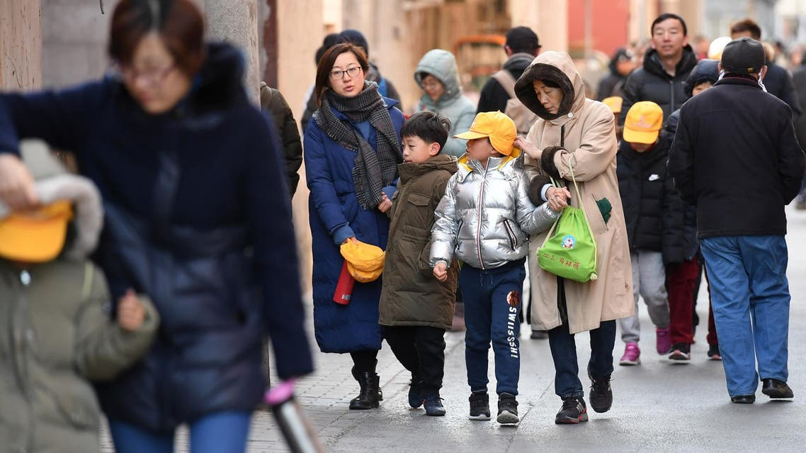 Parents and family members escort their children outside the gates of an elementary school in Beijing following an attack.(AFP)