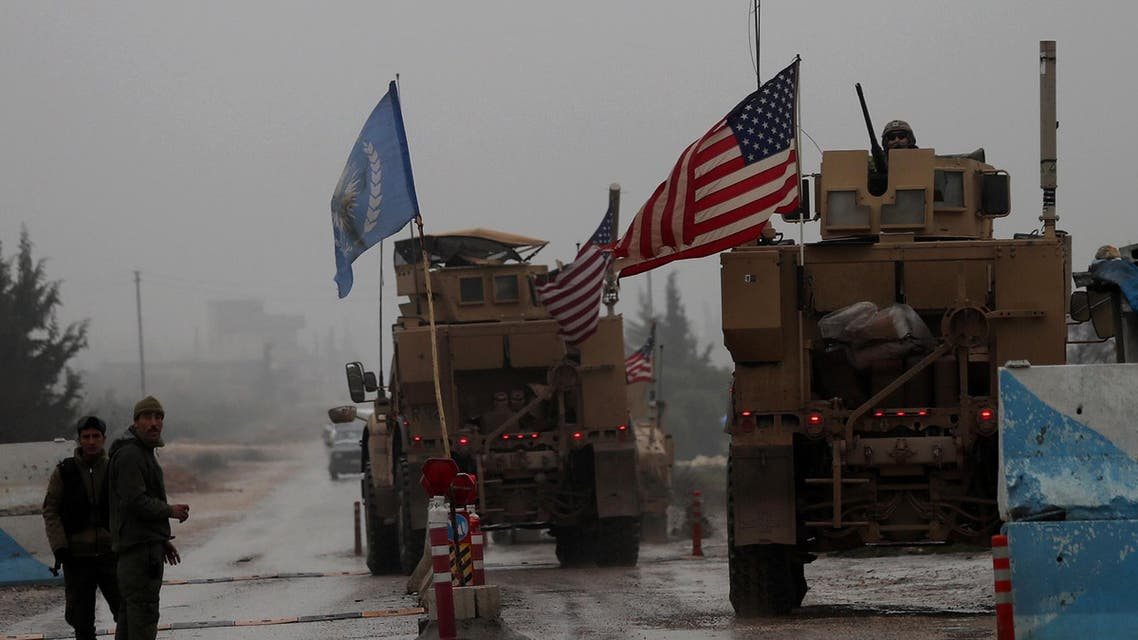 A line of US military vehicles drive through a checkpoint of the Internal Security Forces in Manbij. (File photo: AFP)