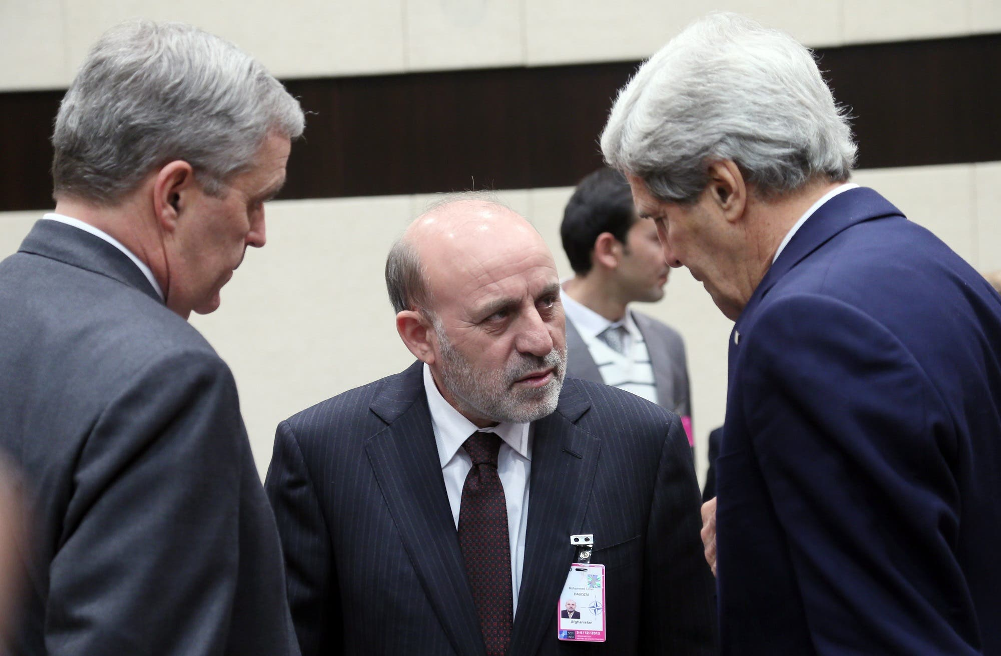 US Secretary of State John Kerry, right, speaks with Mohammed Umer Daudzai, center, during a meeting of NATO foreign ministers in Brussels on Dec. 4, 2013. (AP)