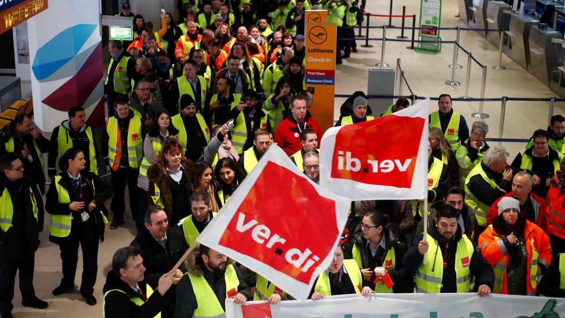 أفراد أمن في مطار كولونيا يحملون أعلام نقابة عمال القطاع العام الألمانية (فيردي) في كولونيا الخميس