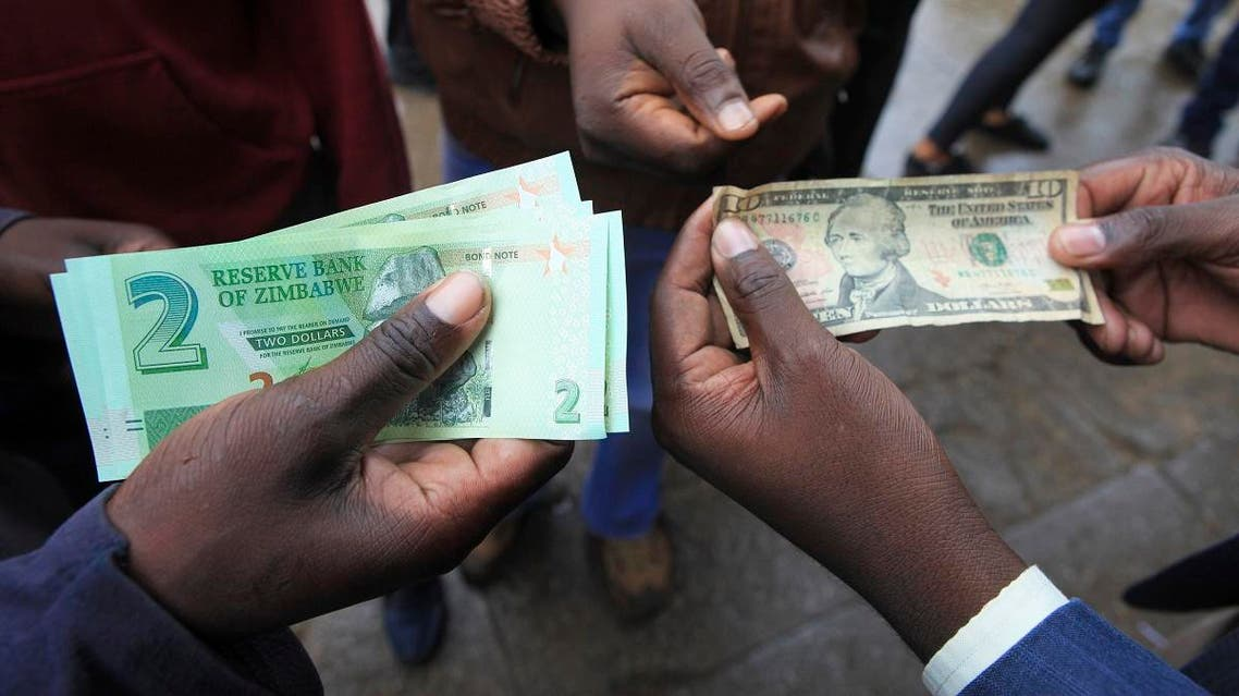 Zimbabweans compare the new note with the US dollar note following the introduction of new notes by the Reserve Bank of Zimbabwe in Harare, Monday, Nov, 28, 2016. (AFP)
