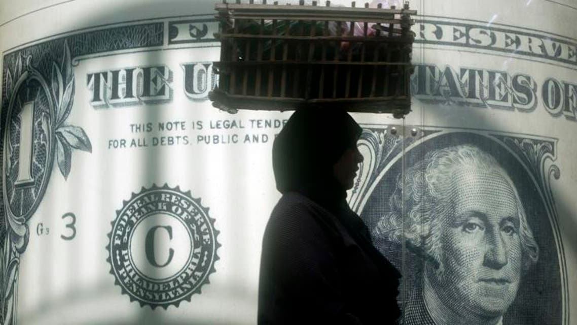 In this Nov. 9, 2016 file photo, an Egyptian vendor walks past a poster depicting a US dollar outside an exchange office in Cairo, Egypt. (AP)